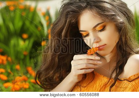 Outdoors Portrait Of Beautiful Teen Girl Smelling Flower, Over Marigold Flowers Field