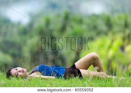Beautiiful young Filipina woman relaxing on green grass lying on her back in a lush green park looking at the camera with a serene smile