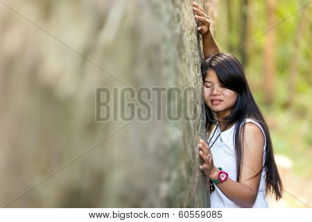 Young Thai girl holding onto a large granite rock with her eyes closed and a serene expression as she meditates and enjoys the peace and tranquility of nature, with copyspace