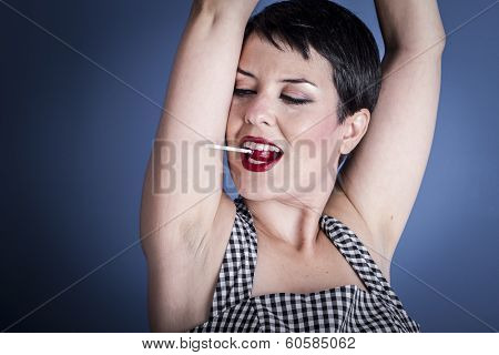 Diet, happy young woman with lollypop  in her mouth on blue background