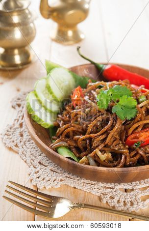 Spicy fried noodles. Indonesian and Malaysian cuisine, mi goreng or mee goreng mamak with wooden dining table setting. Fresh hot with steamed smoke.