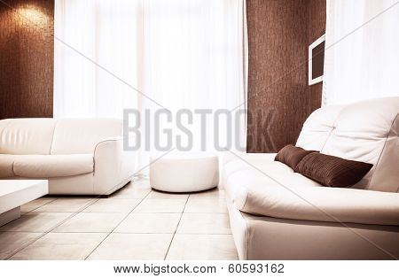Luxury apartment interior in white&brown colors, two stylish leather couch and pouf, bright sun light through big window, cozy flat concept