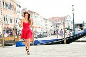 Happy summer girl running in dress in Venice, Italy. Woman smiling laughing joyful having fun by wat