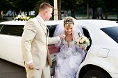 stock photo of limousine  - Happy bride and groom getting out of wedding limousine