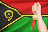 Medal In Hand With Flag On Background - Vanuatu