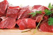 foto of chopper  - fresh raw beef meat slices over a wooden board with dill  - JPG