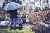 stock photo of deceased  - Widower with his daughter at graveyard looking at grave of deceased mother.