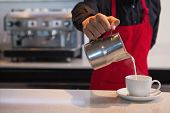 picture of half-dressed  - Barista pouring milk into cup of coffee in a cafe - JPG