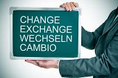 man wearing a suit holding a chalkboard with the words change, exchange, wechseln, cambio written in
