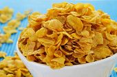 closeup of a bowl with corn flakes on a set table with a blue tablecloth