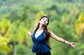 Beautiful young woman embracing the sun standing in a lush green park with her arms outspread and he