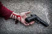 picture of murders  - Man with gun in hand bloodstained lies dead in the asphalt murder victim - JPG