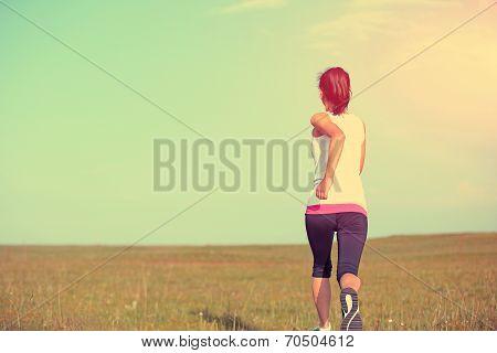 young asian woman runner running on plain grass