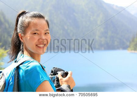 woman tourist/photographe r taking photo with digital camera in jiuzhaigou national park,china