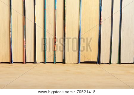 A Number Of Books Standing On A Wooden Surface.
