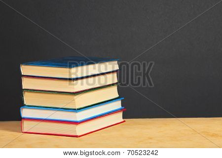 Pile Of Books On A Wooden Surface.