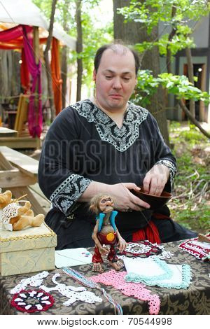 MUSKOGEE, OK - MAY 24: A man checks out a funny troll on his table during the Oklahoma 19th annual Renaissance Festival on May 24, 2014 at the Castle of Muskogee in Muskogee, OK.