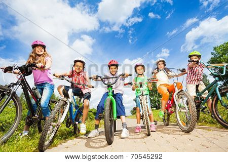 Below angle view of kids in helmets with bikes