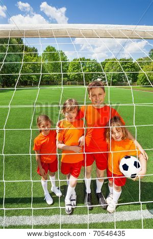 Smiling children standing close with football