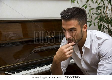 Male Artist Sitting Next To His Upright Piano