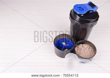 Whey protein powder and plastic shaker on wooden background