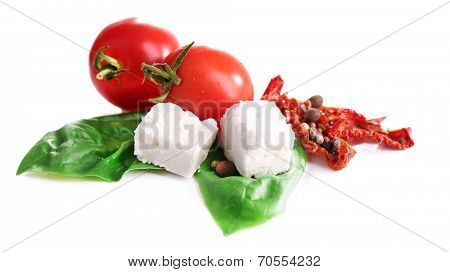 Sun dried tomatoes, feta cheese and basil leaves isolated on white