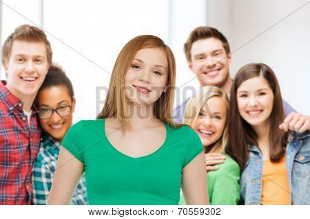 friendship, youth and people concept - group of smiling multiracial teenagers over classroom background