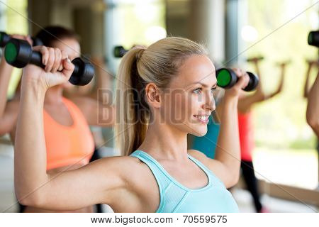 fitness, sport, training and lifestyle concept - group of women with dumbbells in gym