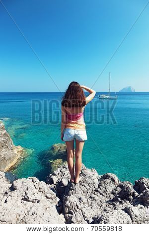 Girl on the rock looking to the horizon