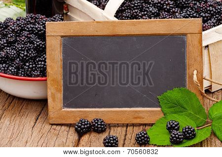 Slate Blackboard In Front Of Ripe Blackberries