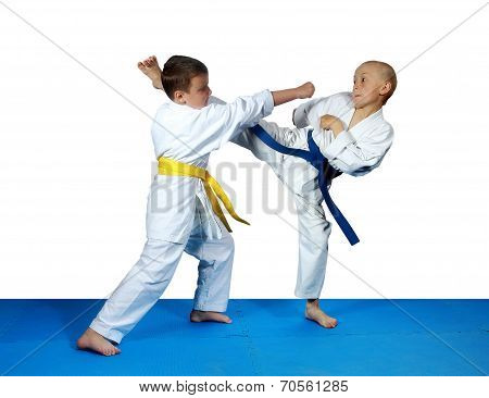 On the blue tatami small athletes are training paired exercises karate