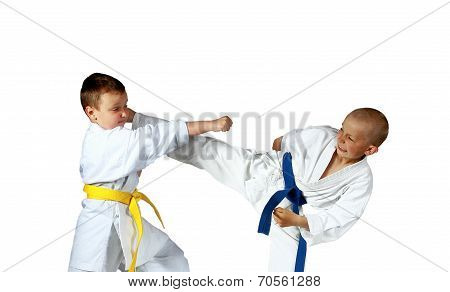 With yellow and blue belts sportsmen are doing paired exercises karate