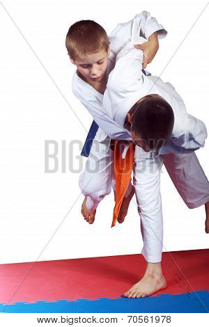 Athlete with orange belt is doing judo throw