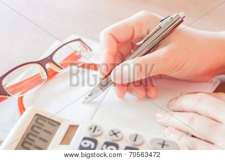 Businesswoman Working With Calculator And Pen