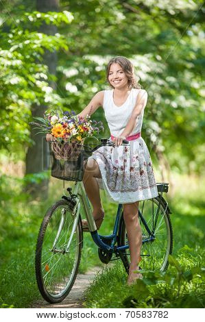 Beautiful girl wearing a nice white dress having fun in park with bicycle. Healthy outdoor lifestyle