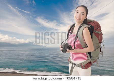 Happy smiling Asian young female backpacker with camera standing in front of Hualien beach, Taiwan, Asia.