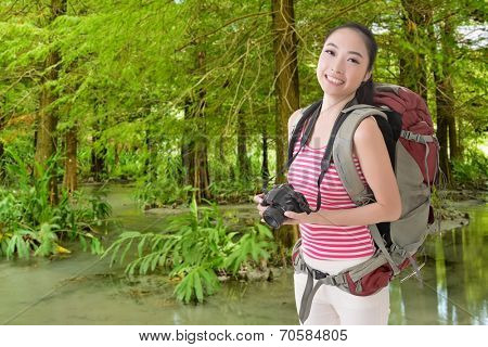 Happy smiling Asian young female backpacker with camera in the forest.