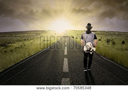 Lonely Guitarist Walking On Road