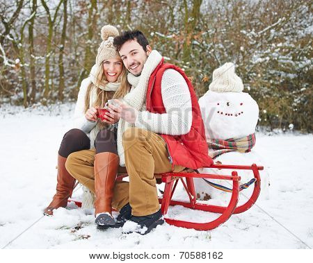 Happy couple in winter drinking tea and sitting on a sled
