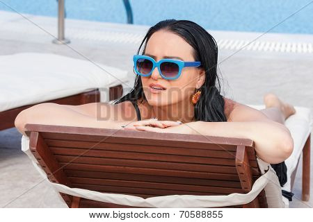 Woman Relaxing On Chaise Longue