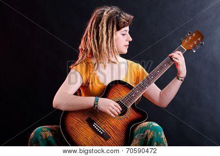 Young Girl With Dreadlocks Playing Guitar