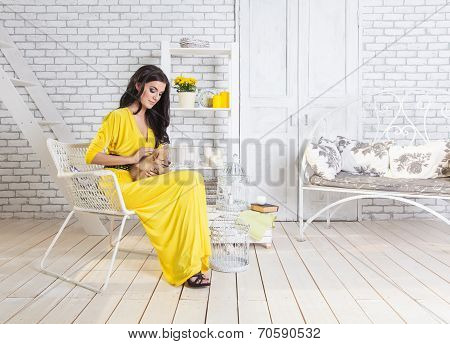 Beautiful Brunette Woman With Small Dog In Hands