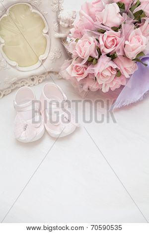 Flowers, Photoframe And Children's Sandals On The Bed