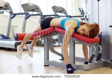 Tired sportswoman lying on sports bench
