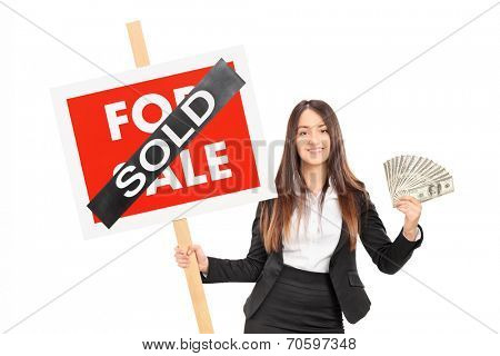 Female realtor holding a sold sign an money isolated on white background
