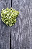 stock photo of broken heart flower  - green heart of flowers on a background of a wooden fence - JPG