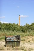 image of dumpster  - The photograph of a dumpster in the middle of the countryside and in front of a chimney - JPG