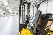 foto of lift truck  - Forklift truck ready to use in a modern storehouse - JPG
