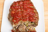 image of meatloaf  - A fresh hot baked meatloaf topped with ketchup on a white cutting board - JPG