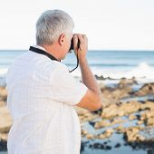 stock photo of take off clothes  - Casual mature man taking a photo of the sea on a sunny day - JPG
